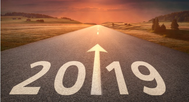 Idyllic open road leading toward setting sun with 2019 written on the road with a big forward pointing arrow.