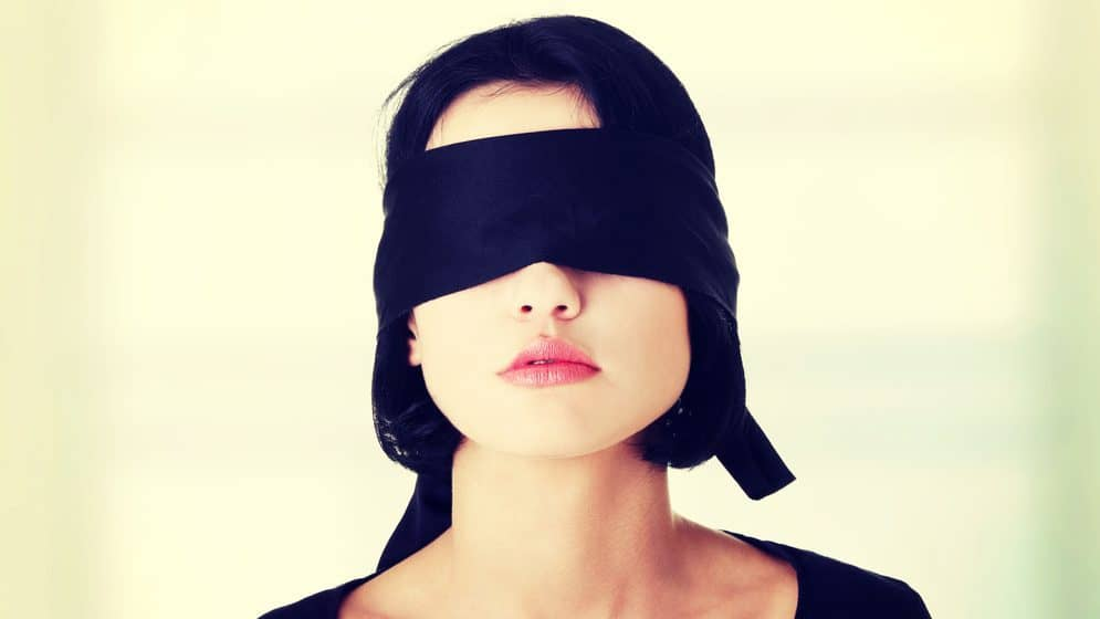 A woman wearing a black fabric blindfold.