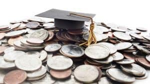 A graduation cap on a pile of American coins.