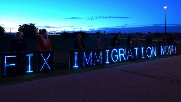 "Lit up letters spelling ""Fix Immigration now"" against a dark blue sky with people standing behind the letters."