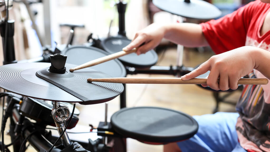 Photo of a young person playing drums. The person's face is not visible, but they are positioned behind the drum set.