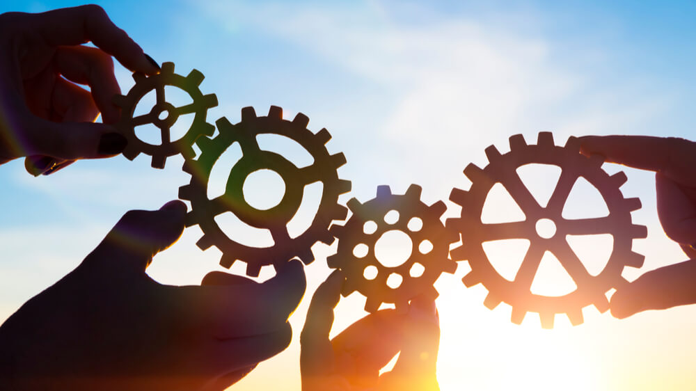 Hands holding gears connected together. They are in the shadow of the sun against a blue sky.