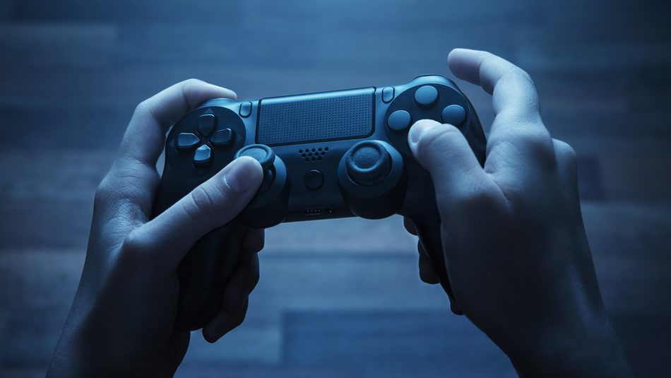 dark-lit photo of a pair of hands holding a video game controller