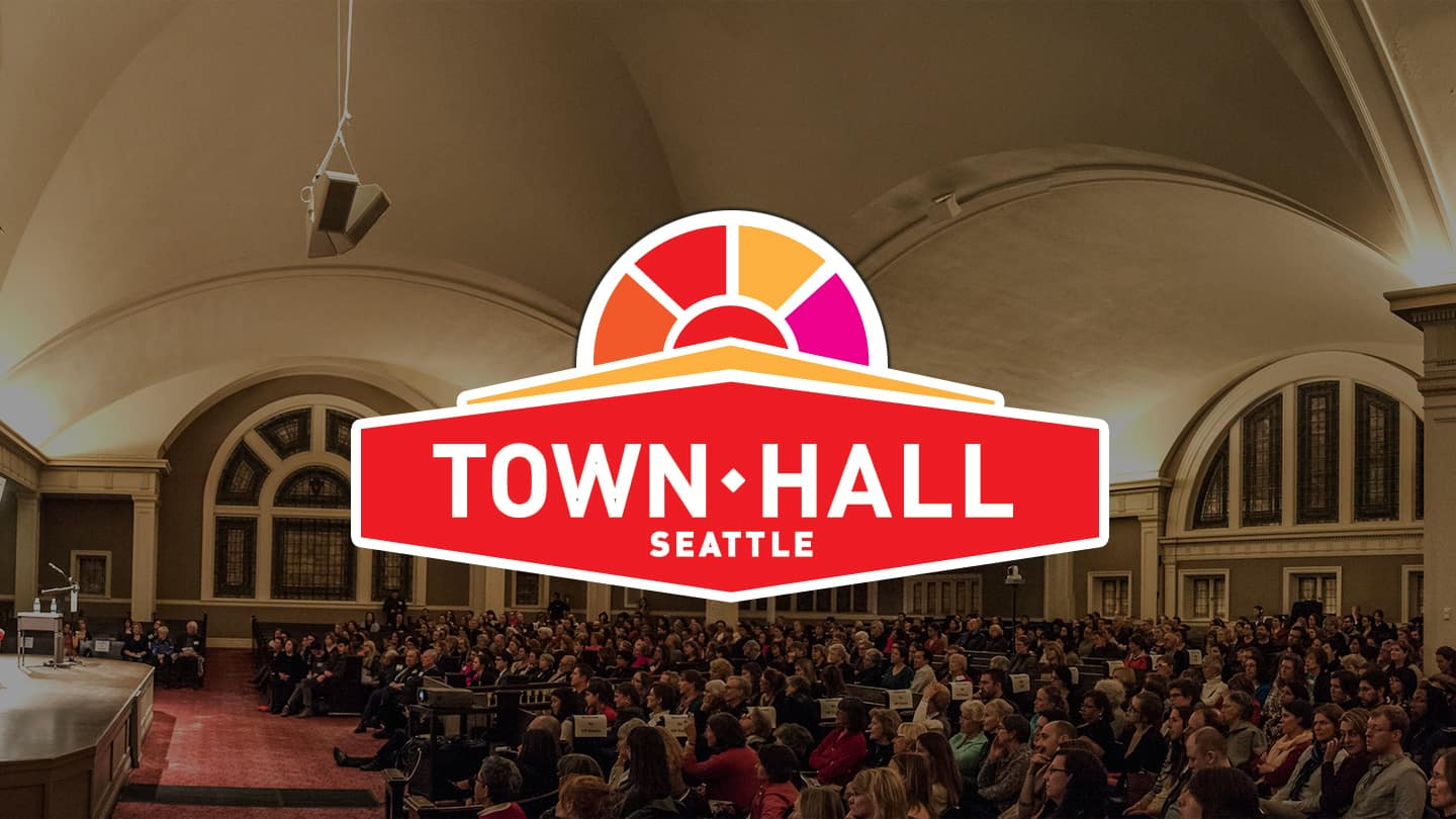 Town Hall Seattle Logo with a filled auditorium in the background.