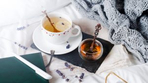 A cup of tea and pot of honey, a notebook and pen, and a blanket resting artfully on a bed, indicating relaxation.