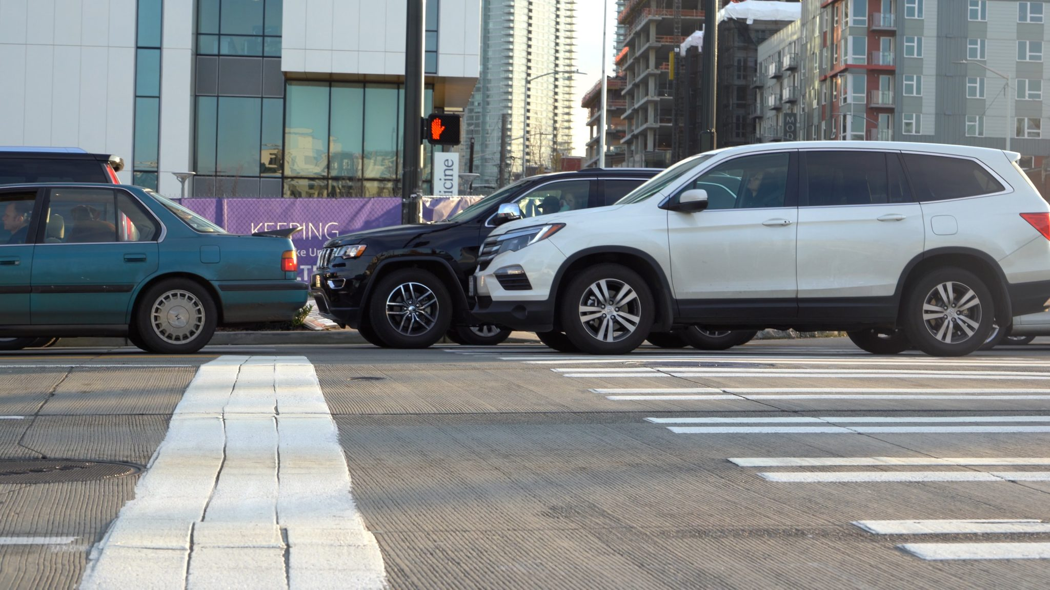 Several cars blocking the curb ramp at the other end of a crosswalk.