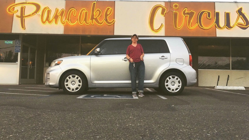 Photo of Christian standing in front of his car, which is parked sideways across accessible spots, in front of a restaurant called Pancake Circus