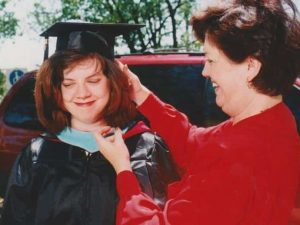 Lisa Ferris in a graduation gown. Her mother is helping her adjust her cap. They are standing outside in front of a red vehicle.
