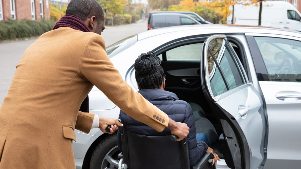 a man pushes a woman's manual wheelchair, helping her towards a car with the door open