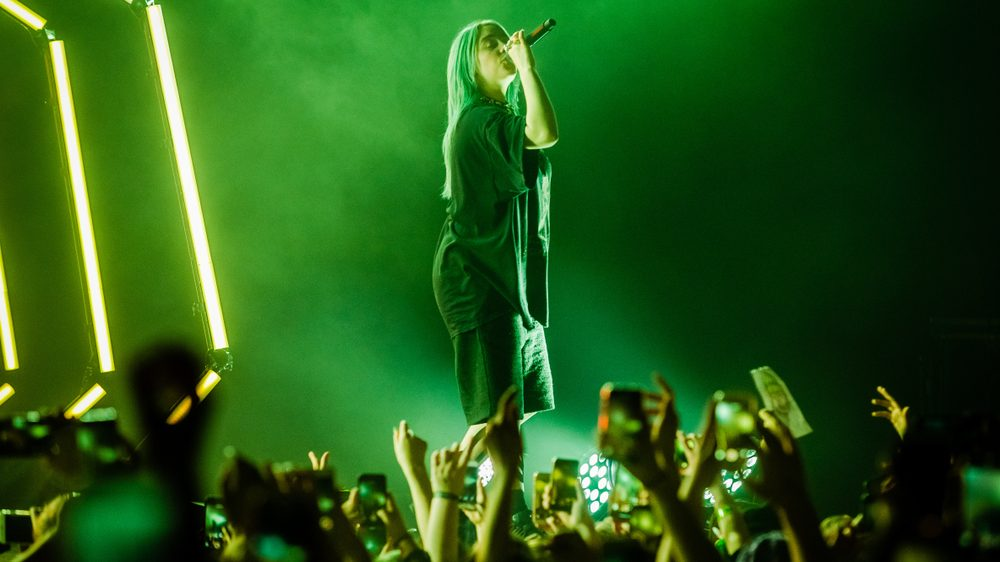 green toned photo of Billie Eilish singing on stage to a crowd