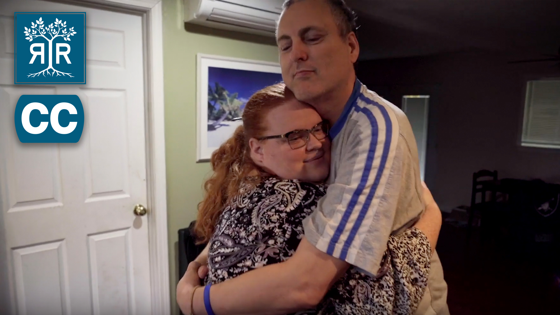 A middle aged white man hugs a white woman with red hair.