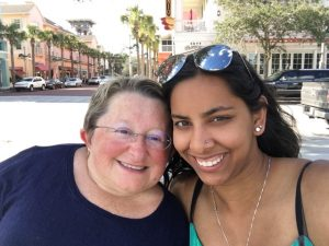 Image of Karen and Anita. They are outside and are close together for the photo and smiling into the camera.