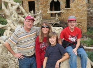 Family photo of the Petty family - 4 individuals (2 children and 2 adults) are smiling and facing the camera. They are outside and positioned in front of an abstract statue.