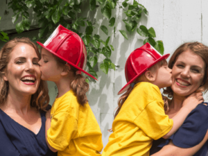 Two white women who appear to be twins hold identically dressed children in yellow shirts with firefighter hats.