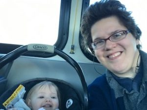 Ivanova is smiling into the camera. To the left is a smiling baby in a car seat.