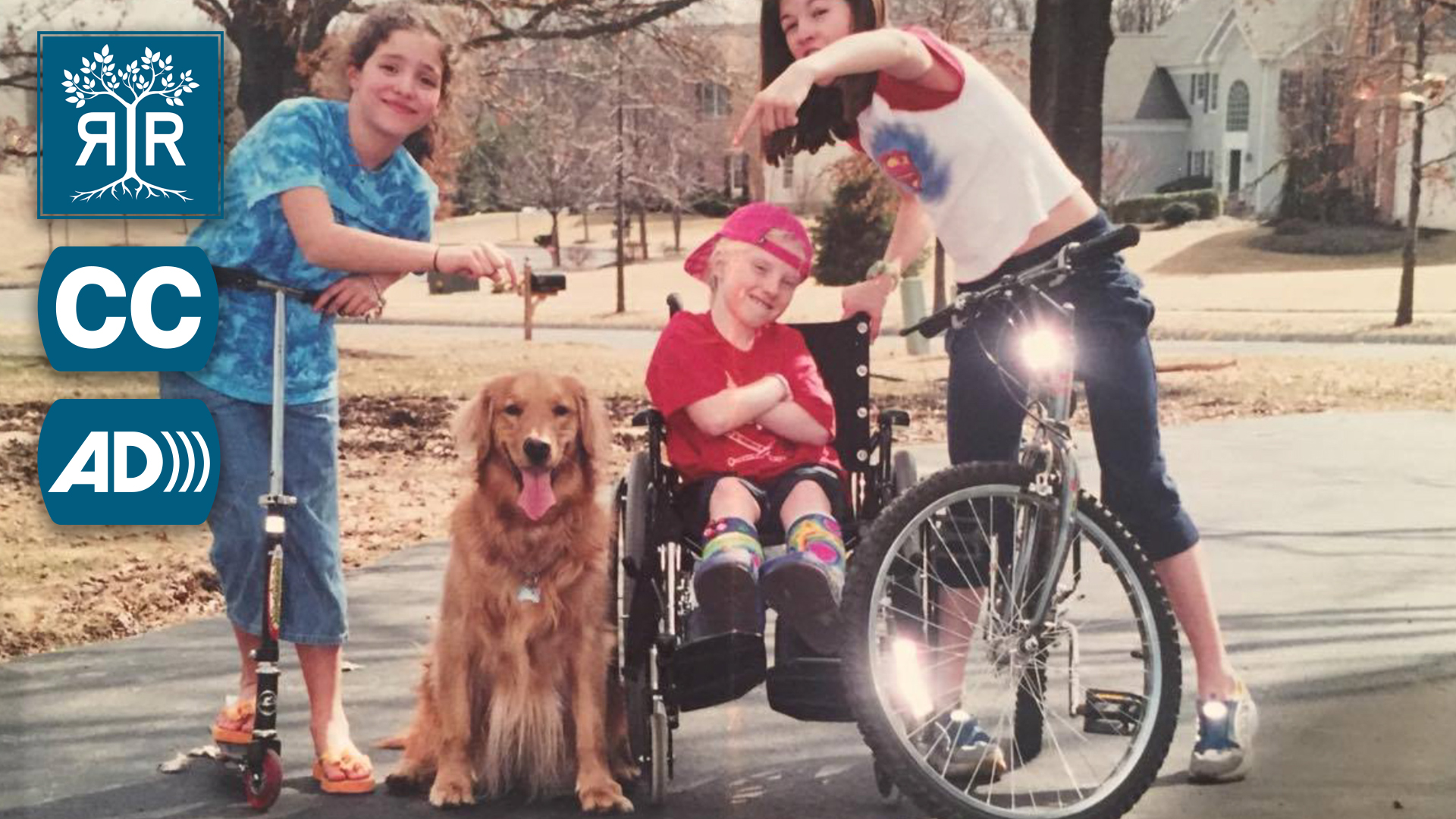A young Daisy poses in their wheelchair with two friends and a panting golden retriever.
