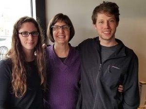 Photo of Debra Kahn and her two children with their arms around each other, smiling.