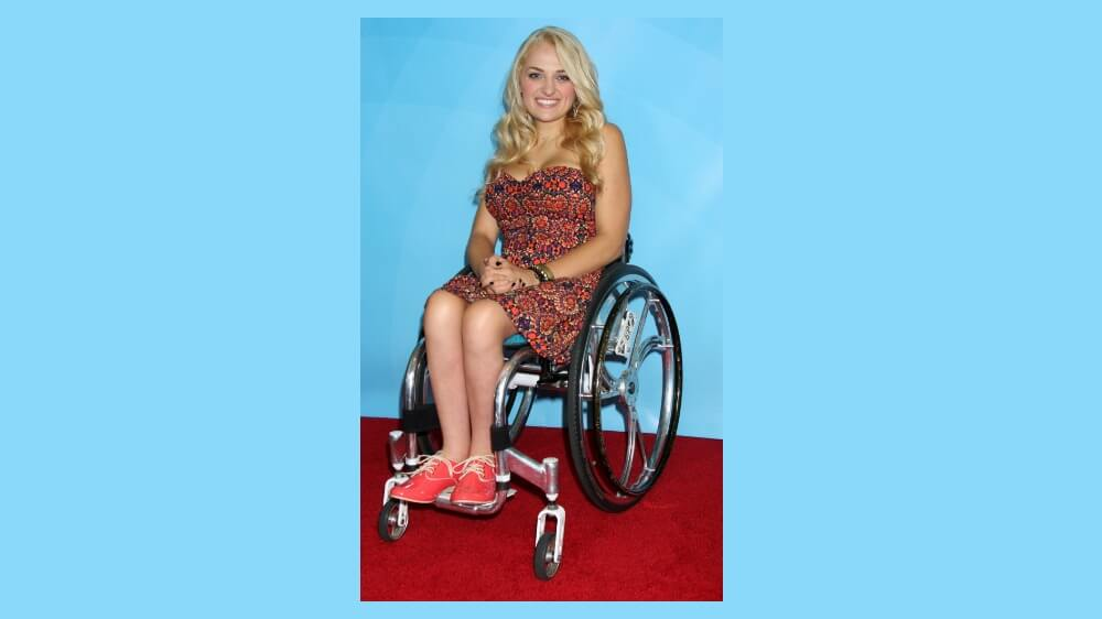 Photo of Ali Stroker, a blonde-haired white woman in a wheelchair.