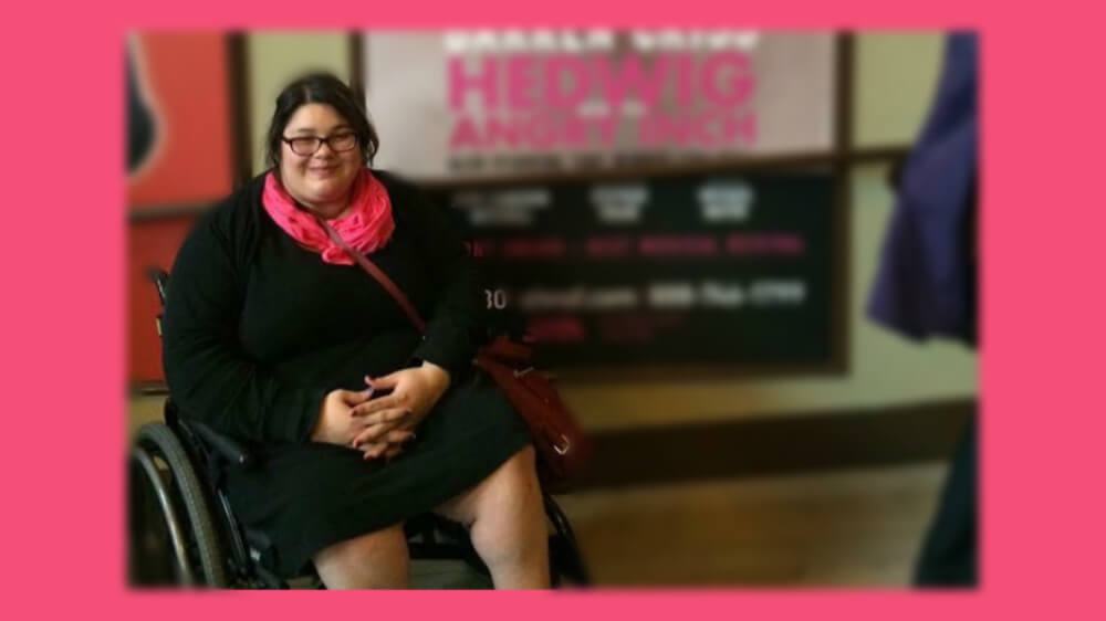 Photo of Yolanda in a black dress and pink scarf sitting in a manual wheelchair