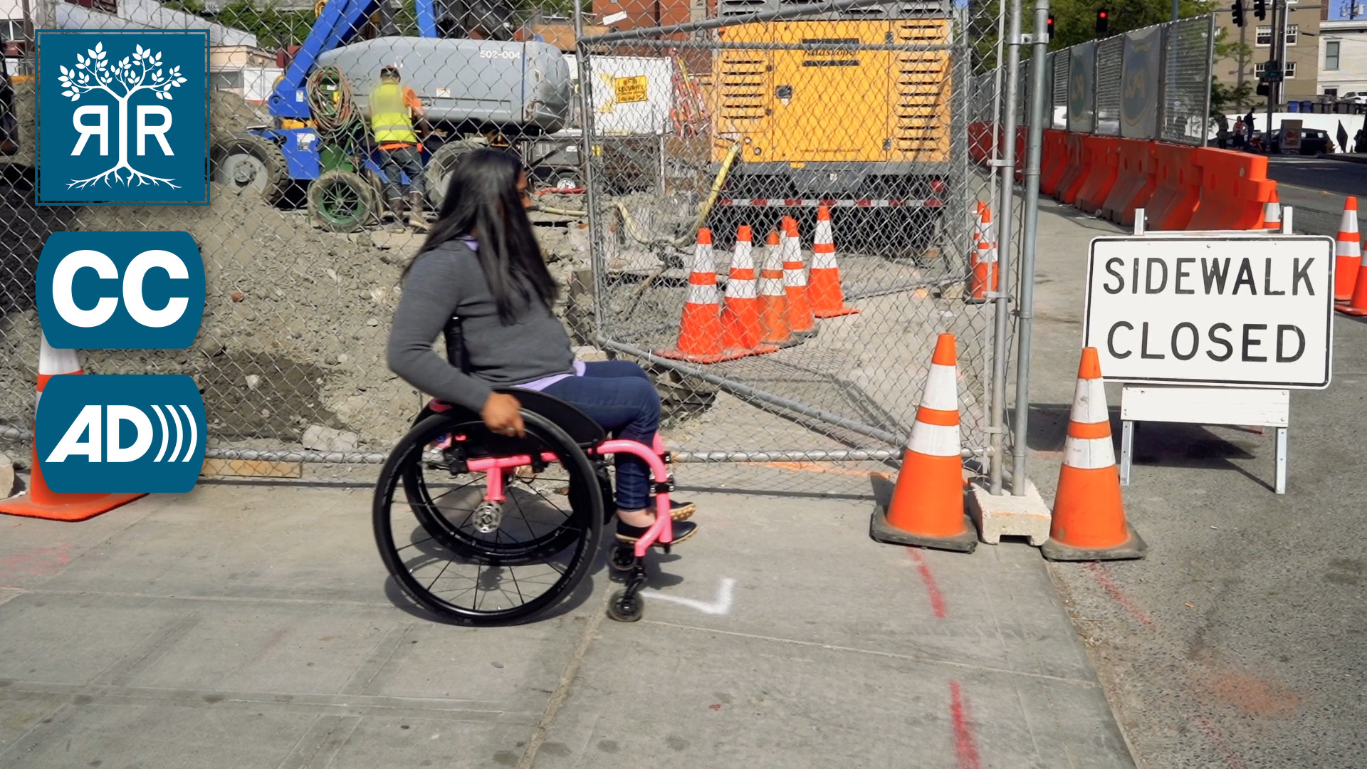 "A woman with long black hair pushes her wheelchair towards a sign that says, ""Sidewalk Closed"", infornt of a construction site."