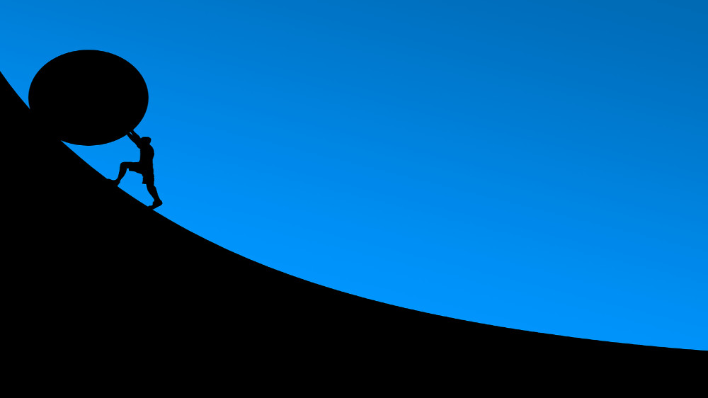 A silhouette of a person pushing a round object that's much bigger than they are up a steep incline.