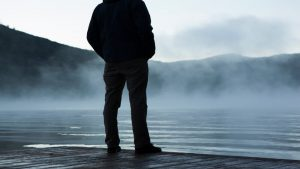 A person standing alone, looking out onto a hazy lake.