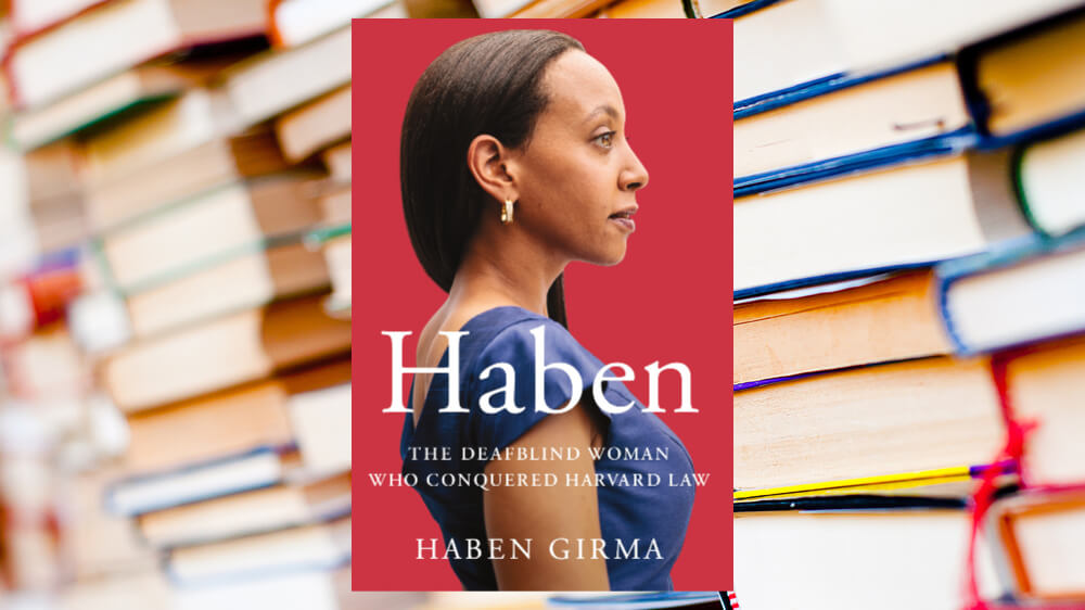 A photo of Haben Girma's book cover positioned over a background of piles of books.