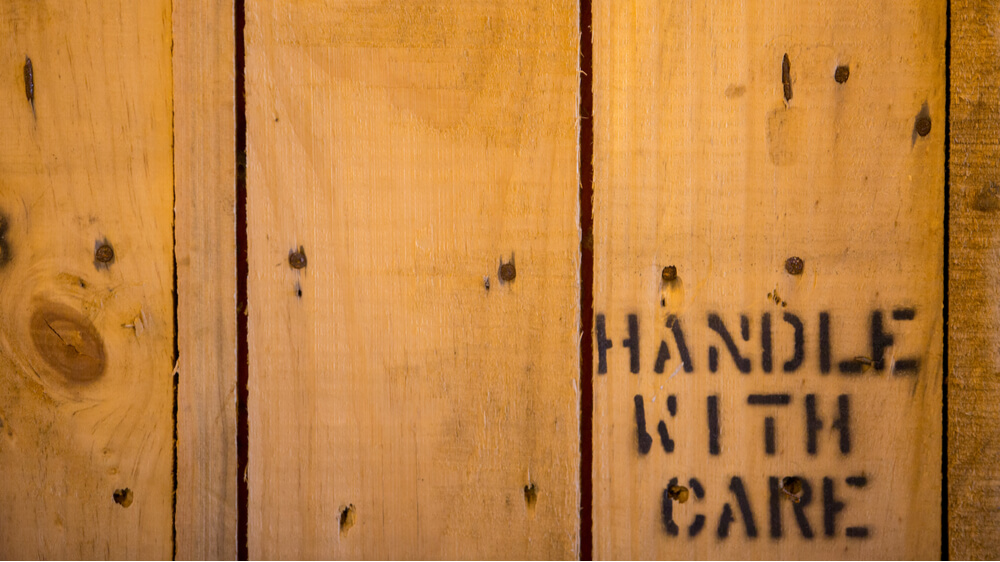 "Wooden shipping crate with the words ""handle with care"" printed on it."