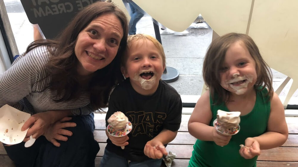 Photo of Heather and her two children, both with ice cream on their faces.