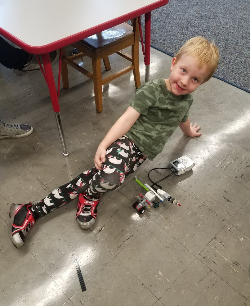 Photo of the author's son on a classroom floor next to a small robot.