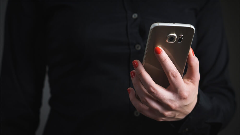 Photo of a person with red-painted fingernails holding a smartphone. On the person's torso/hand is showing.