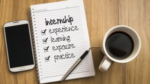 """Photo of a smartphone, a notebook and pen, and a cup of coffee on a wooden table. Written in the notebook is """"internship, experience, learning, exposure, practice."""""""