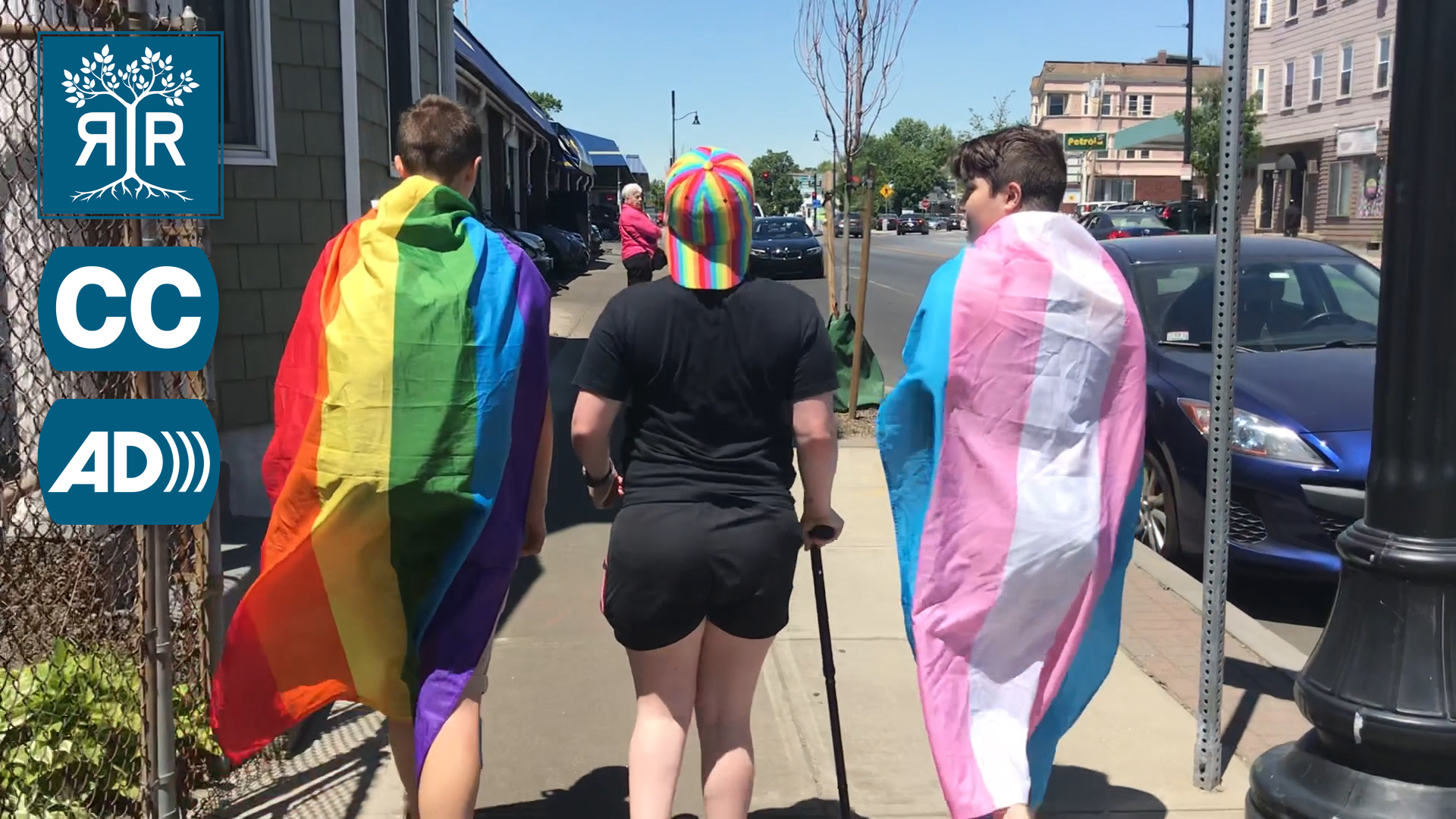 Image of Daisy walking with two friends, Daisy is in the middle of the group. On the back of the person on the left is the gay flag. On the back of the person on the right is the trans flag.