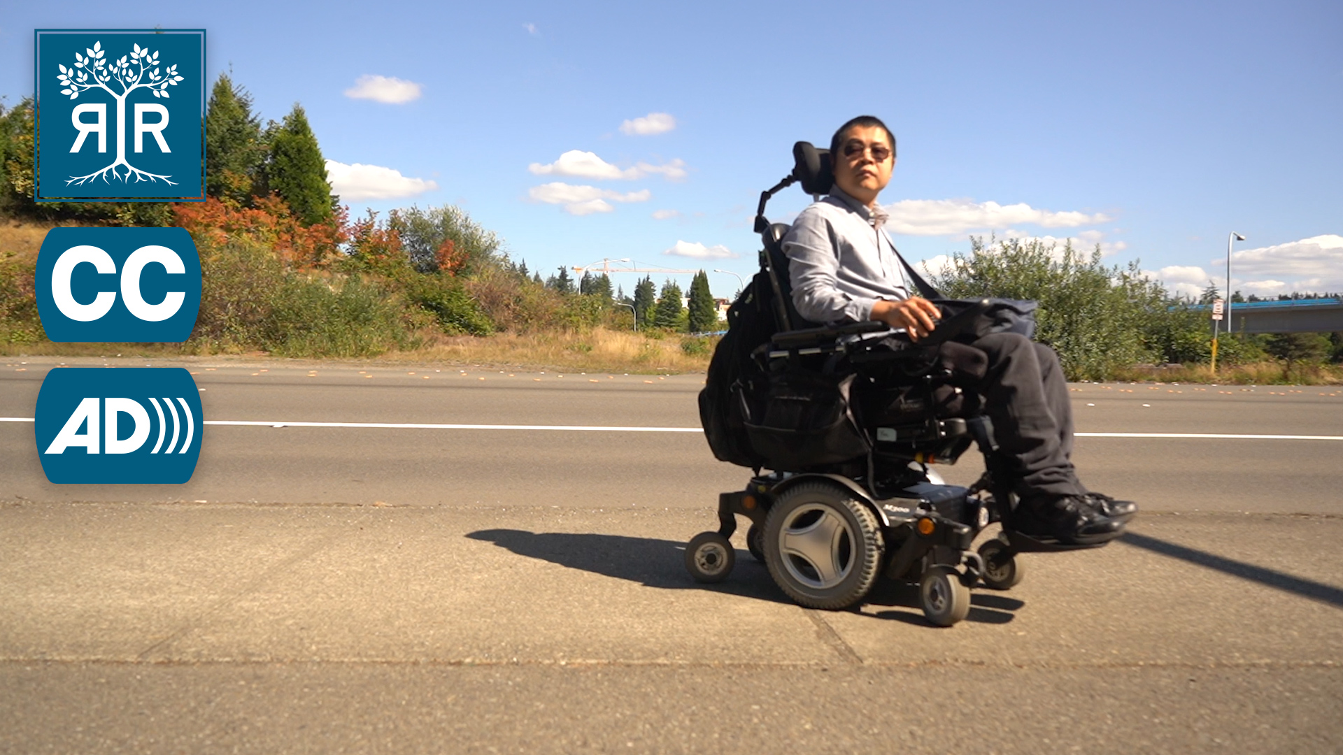 Image of Dixin in their wheelchair. They are positioned on the highway.