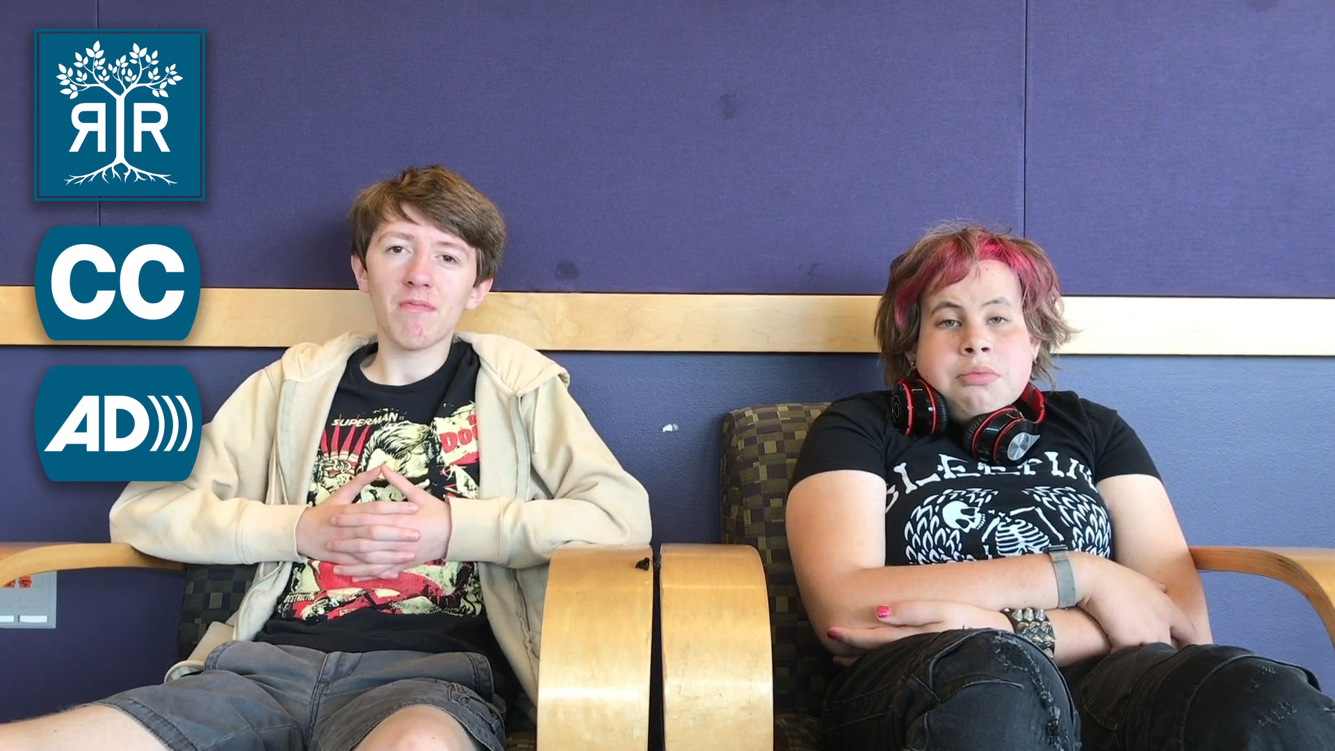 Two students sit in chairs facing the camera