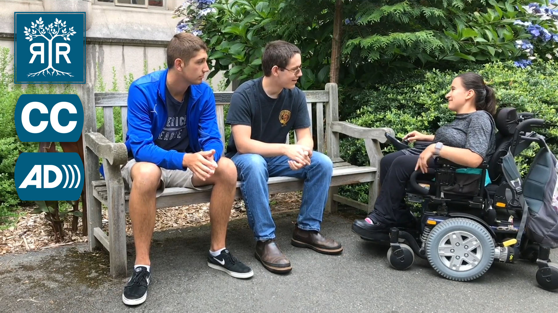 Two students face another who uses a power chair.