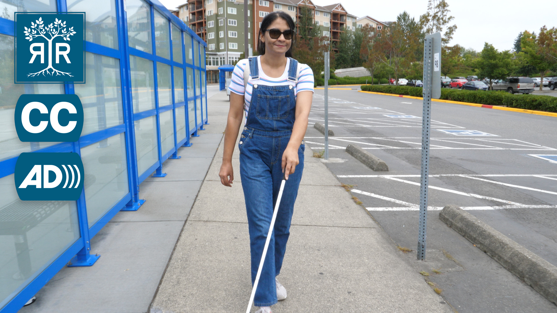 Amandeep walking on the sidewalk with their white cane