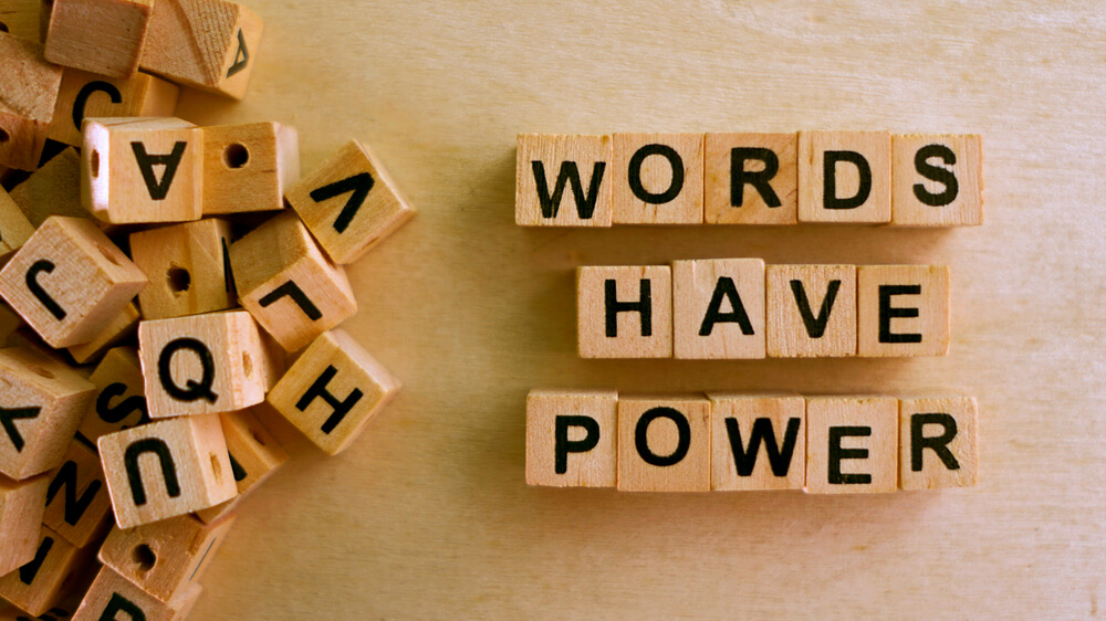"Letter tiles spelling out ""words have power."""