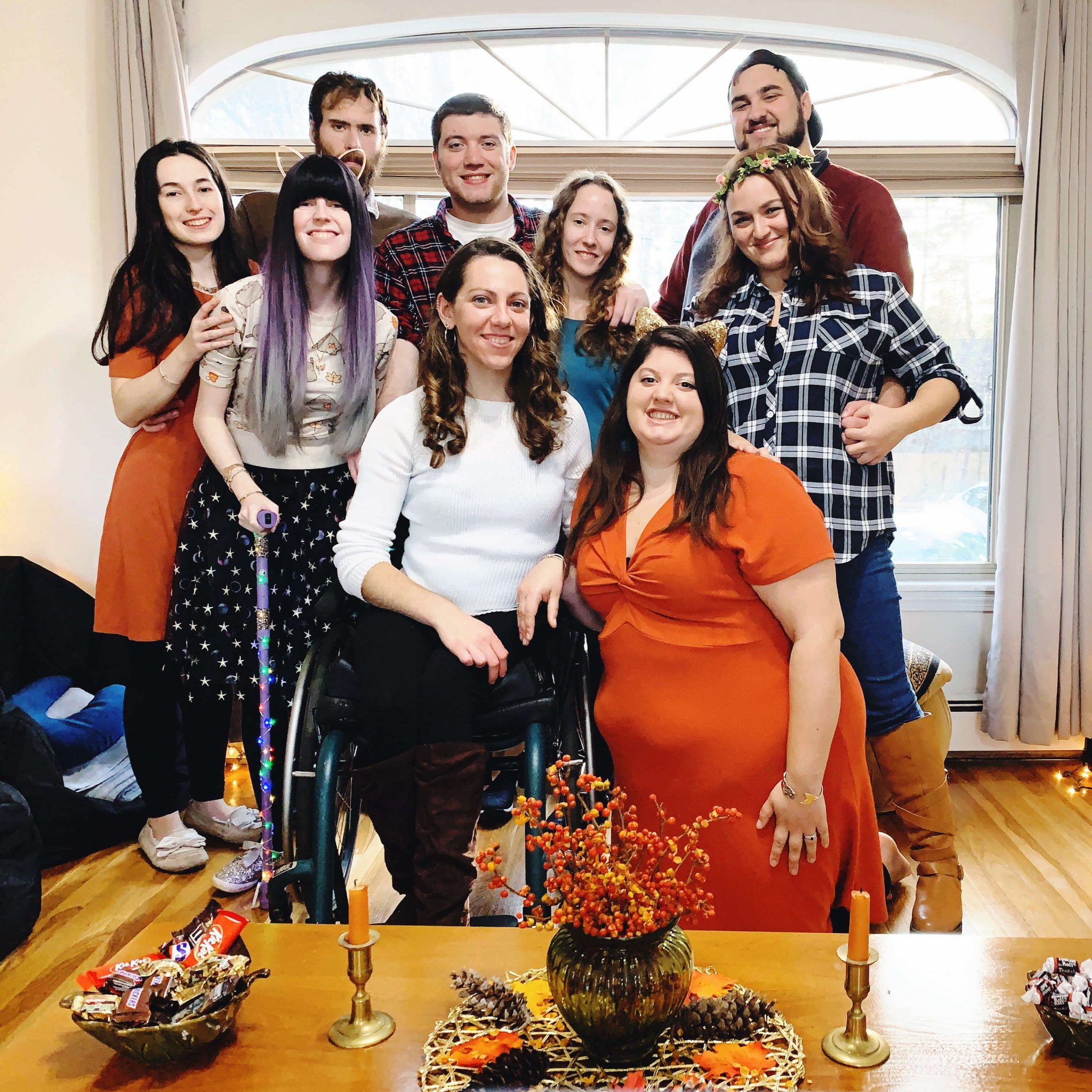 The writer is posing with her group of friends for Friendsgiving inside a home with a large window behind everyone. In front, there is a small table with centerpieces and fall-inspired decor, including orange candlesticks. Several people are wearing fall attire, including two orange dresses, a few flannel shirts, a flower crown, a fall sweater with leaves on it, and a purple walking cane decorated with rainbow holiday lights. Everyone is smiling.