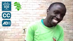 Rooted in Rights and Mental Voices Africa logos with Closed Captioning and Audio Description logos. Festus smiles in front of a brick wall.