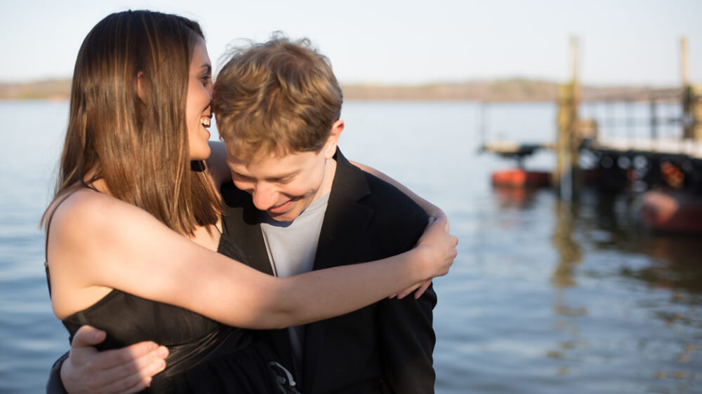 The author and her husband, two smiling white individuals, hug each other in front of a lake. Sarah, who has straight, medium-length brown hair and is wearing a black and white floral dress, speaks into his ear. Her husband, who has wavy, close-cropped dark blonde hair, and is wearing a gray shirt and black suit jacket, bends his head, as if to listen.