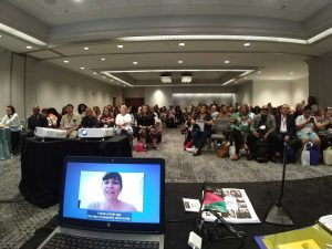 A view of the audience as Rooted in Rights presents at the National Council for Independent Living. On a laptop screen, a disabled parent talks with the audience.