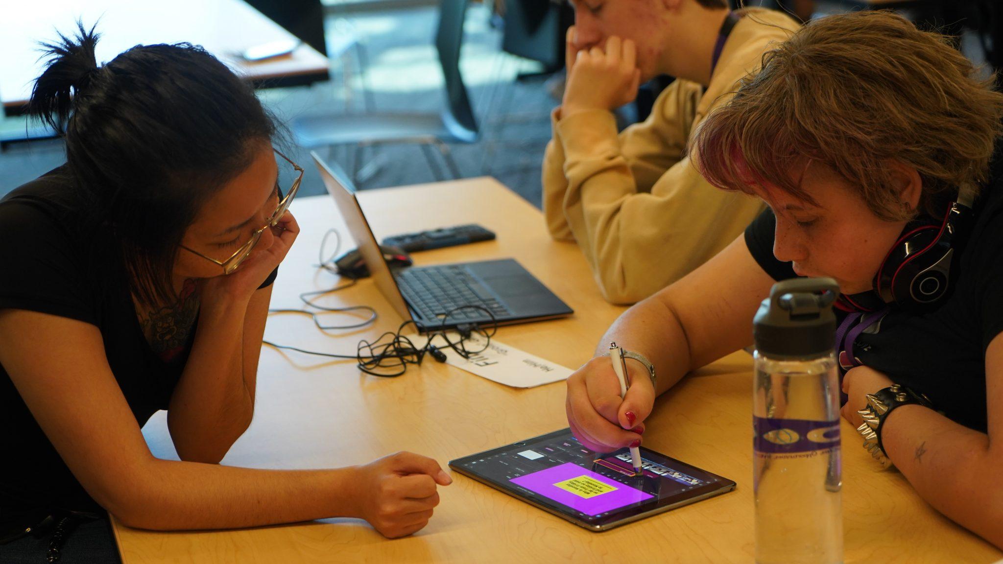 Rachel watches a DO-IT Scholar edit a video on an iPad.