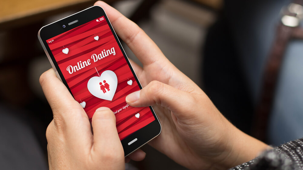 Photo of a person's hands holding a smartphone that has an online dating app opened