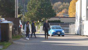 A blue car passes three pedestrians in the street.