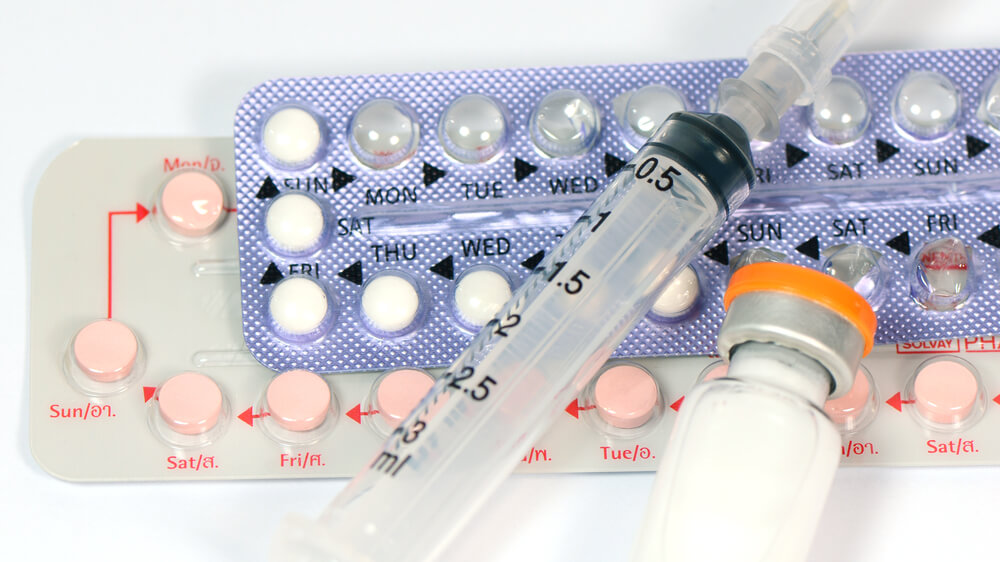 Two packs of birth control pills and a syringe with a medicine bottle