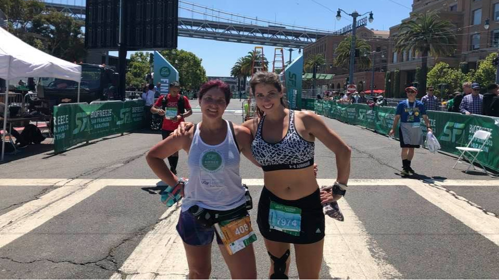 Photo of Amy and friend, both pausing from running.