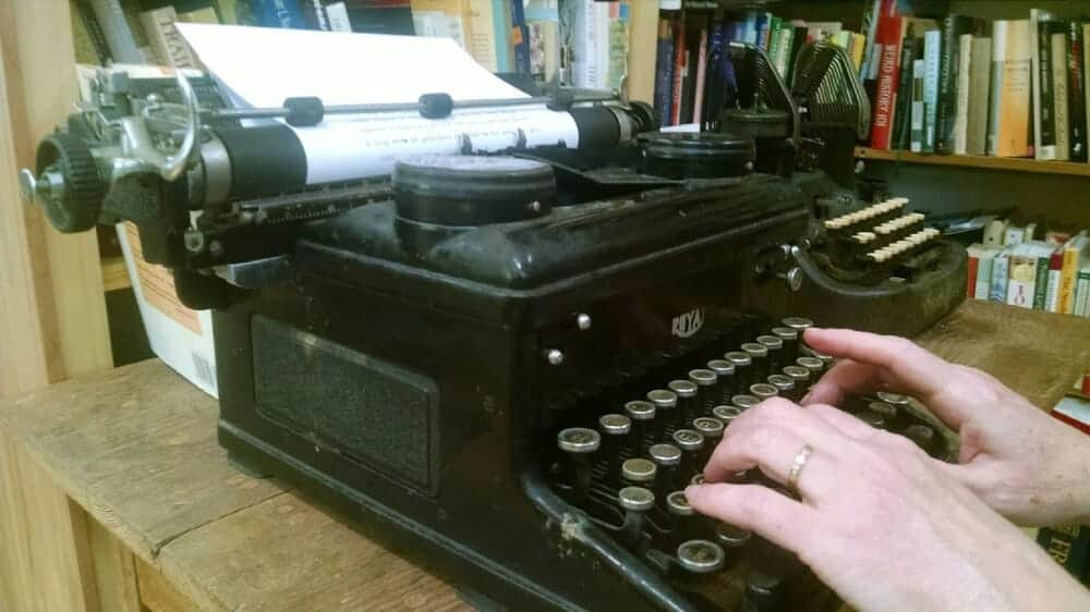 Photo of hands typing on an old black typewriter.
