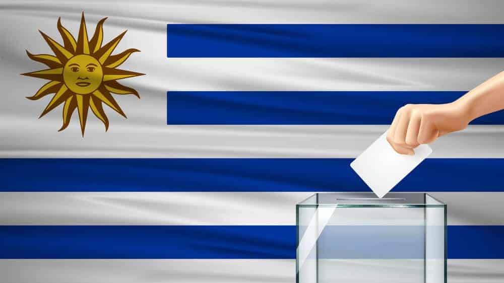 Uruguayan flag with a ballot box in front of it and a hand dropping in the ballot.