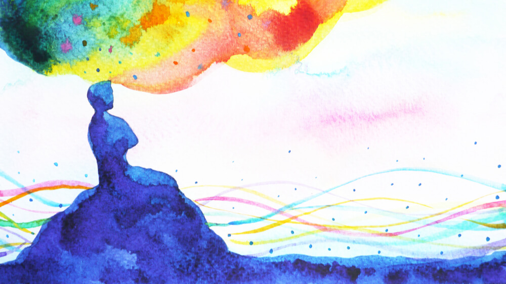 An abstract watercolor of a person sitting atop a hill with a rainbow cloud of thoughts emanating from their mind.